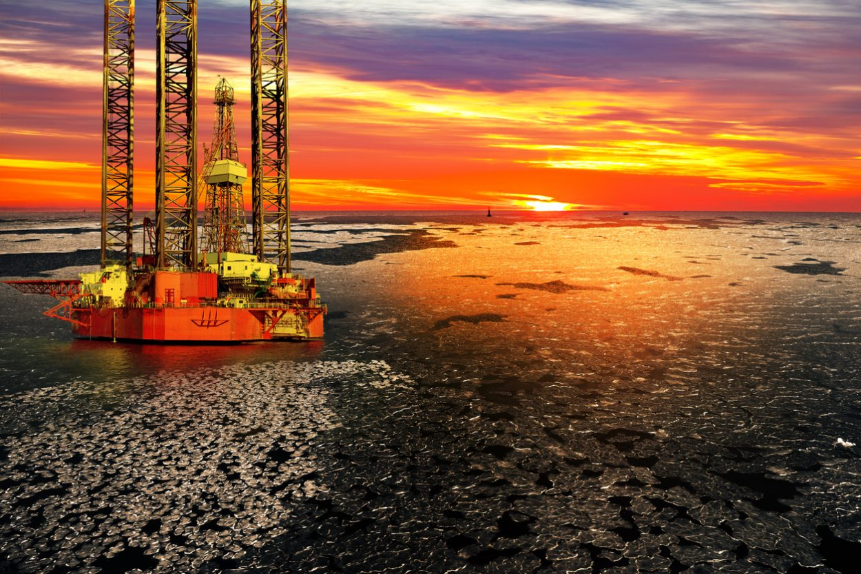 Offshore oil and rig platform in sunrise on frozen sea/ iStock